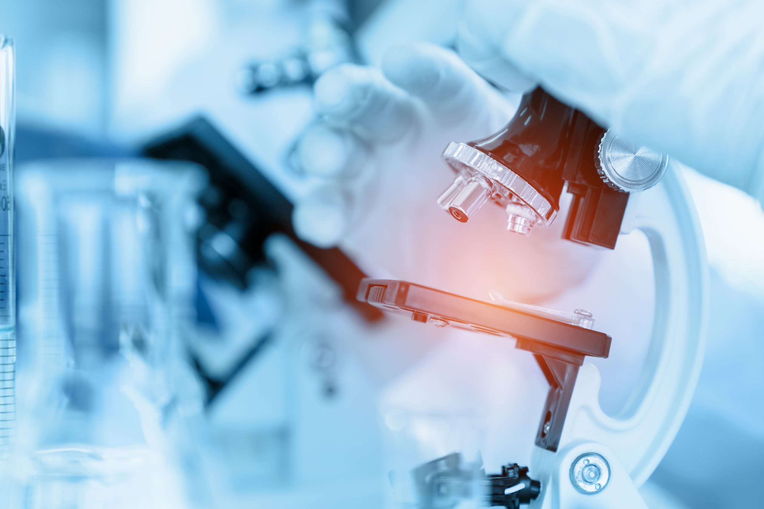 Close Up Scientist using microscope in laboratory room while mak